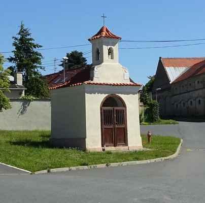 Bašť - kaple se zvoničkou - AB - Pozdně barokní kaple se zvoničkou stojí uprostřed obce na Návsi. Kříž uvnitř kaple s ukřižovaným Kristem pochází z 2. třetiny 18. století. Rekonstrukce kaple proběhla v roce 2009.