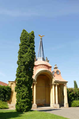 """Gloriet Ploskovice - Gloriet pochází z roku 1731. Jedná se o sochami zdobený altán, pro který je typické sloupové loubí. Původní barokní podoba glorietu se zachovala až do období protektorátu. V této době byl přeměněn do karikaturní podoby """"brány s vrátnicí"""". Mezi lety 2003 a 2006 proběhla rekonstrukce památky, která vrátila glorietu původní podobu."""